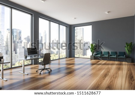 Corner of modern office waiting room with gray walls, wooden floor, row of green armchairs and computer table with armchair. 3d rendering