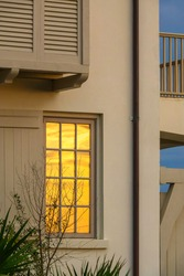 Corner of multistory beach house with tall window that reflects sky glowing at sunset along the Gulf Coast in the Florida Panhandle