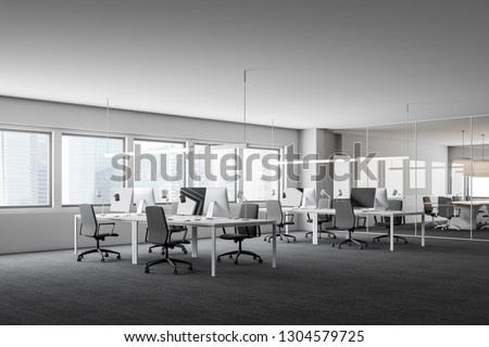 Corner of open space office with white walls, carpeted floor and rows of white computer tables with gray chairs. 3d rendering