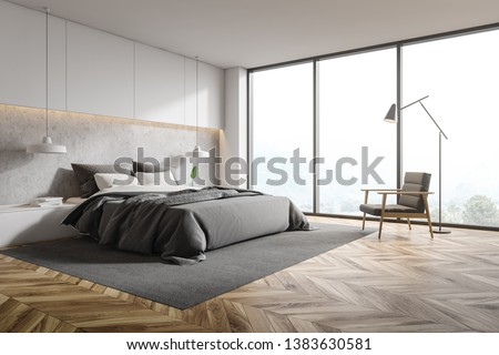 Corner of panoramic bedroom with white and concrete walls, wooden floor, gray master bed with bedside tables and gray armchair with floor lamp above it. 3d rendering