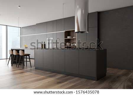 Corner of panoramic kitchen with concrete walls, wooden floor, dark gray island with built in sink and cooker, gray cupboards and bar with stools. 3d rendering