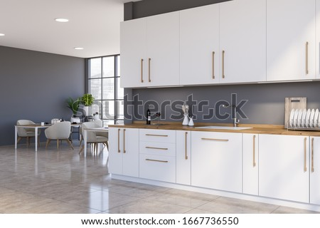 Corner of spacious panoramic kitchen with grey walls, tiled floor, white countertops and cupboards and dining tables with white armchairs in background. 3d rendering