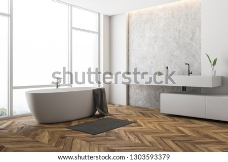Corner of stylish bathroom with white and concrete walls, big window, wooden floor, white bathtub with towel on it and long white sink. 3d rendering