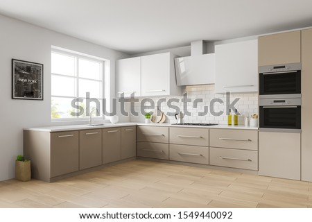 Corner of stylish kitchen with white and brick walls, wooden floor, beige countertops with built in sink and cooker, white cupboard and picture with New York cityscape. 3d rendering