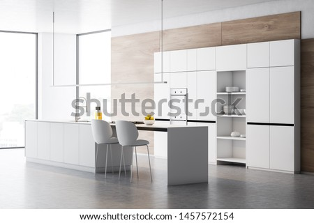 Corner of stylish kitchen with wooden walls, concrete floor, white cupboards with built in ovens and white island with sink, cooker and chairs. 3d rendering
