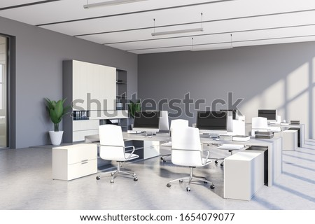 Corner of stylish open space office with grey walls, concrete floor, row of white computer tables with chairs and white bookcase with folders. 3d rendering Foto d'archivio ©