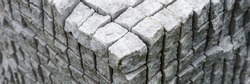 Corner of the concrete cuboid made of gray uneven stones