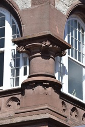 Corner of the house with sandstone column in the style of historicism