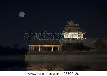 Corner turret of the Forbidden City asurrounded by Moat,  at night. Beijing, China.