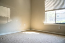 Corner view of clean apartment bedroom with window view, natural light and vacuuming rough carpet. Typical apartment bedroom detail in America.