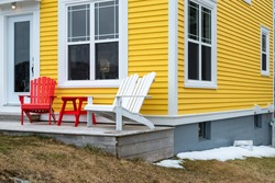 Corner view of the exterior of a vintage yellow wooden clapboard house with red and white Adirondack chairs on the patio. The building has multiple windows and a white glass door.