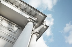 Corner with white pillars of classical portico under cloudy sky on a sunny day. Old classic architecture example. St. Petersburg, Russia