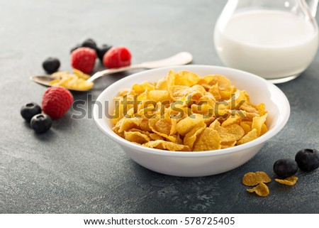Cornflake cereals in a bowl with milk on blue background, quick breakfast #578725405