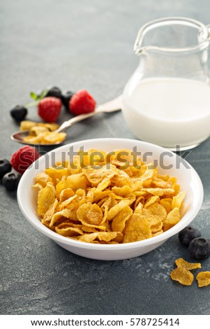Cornflake cereals in a bowl with milk on blue background, quick breakfast #578725414