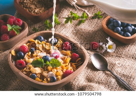 Cornflakes and other cereals with fresh fruits of raspberries, blueberries and pouring milk on healthy breakfast.  #1079504798