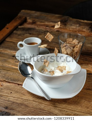 Cornflakes are falllig into the bowl with milk. Glass of dry cornflakes and coffee on wood background #1208339911