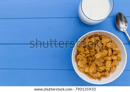 Cornflakes breakfast cereal bowl with milk on wood table background with copy space #790135933