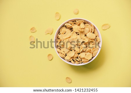 Cornflakes breakfast in bowl on yellow background for cereal healthy food - top view  #1421232455