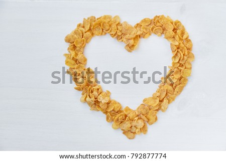 Cornflakes on a painted white wooden background. The symbol of the heart is laid out of cornflakes. #792877774