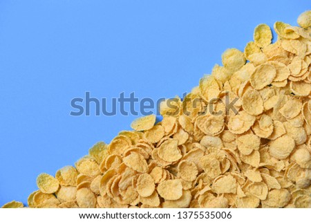 Cornflakes texture on blue background top view / Breakfast cornflake cereal #1375535006