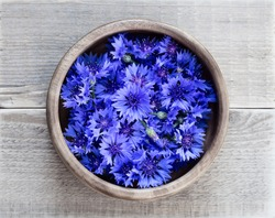 Cornflowers in a wooden bowl on a wooden table. Flowers Cornflowers collected for drying. Herbal tea cornflower buds