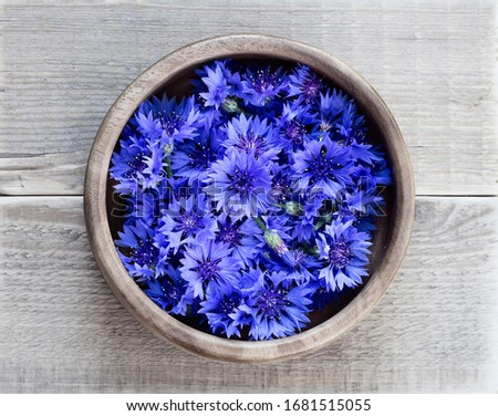 Cornflowers in a wooden bowl on a wooden table. Flowers Cornflowers collected for drying. Herbal tea cornflower buds Foto stock ©