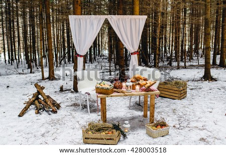 Cornice with white curtains , wooden crates with hay, pine wood, white fur covered chairs, a table with bread and romantic candles. Picnic in the winter