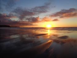 Cornish sunset reflecting on wet sand at Perranpoth.