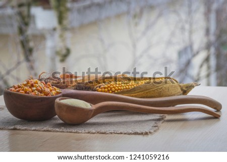 Cornmeal and grain in wooden spoons on a linen napkin #1241059216