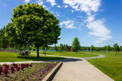 Cornwall, Ontario/ Canada - June 6th, 2020:  man rests on a bench in a beautiful park landscaping in Lamoureux Park