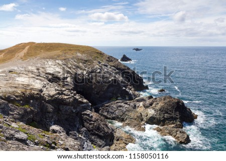 Cornwall rugged and rocky coastline on a slightly cloudy grey summer's day