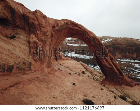 Corona Arch, sandstone arch with snow in the background near Moab Utah #1121176697
