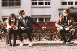 corona covid-19 social distancing concept picture with three people wearing face masks - stay away