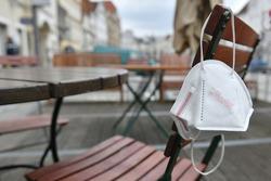 Corona crisis - lockdown - FFP2 mask hangs on a chair in an empty beer garden in Steyr, Austria, Europe