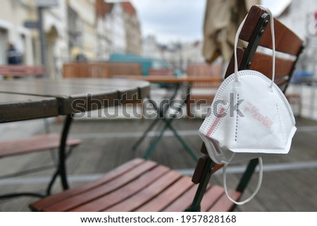 Corona crisis - lockdown - FFP2 mask hangs on a chair in an empty beer garden in Steyr, Austria, Europe Stok fotoğraf ©