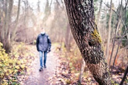 Corona depression, anxiety, loneliness and social distancing concept. Lonely sad man walking in forest alone during coronavirus isolation wearing a mask. Mental health issues and stress from virus.