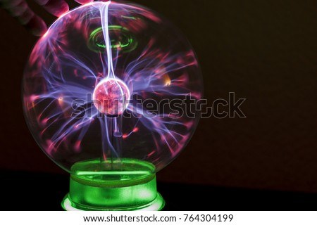 Corona discharge in a gaseous medium with the example of fingers and coil Tesla. Plasma ball. #764304199
