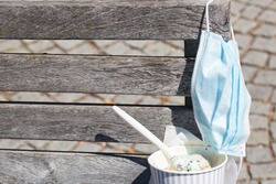 Corona summer concept. Disposable face mask and cup with mint ice cream and plastic spoon on wooden bench