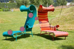 Corona summer concept. Virus on green cast-iron garden lounge chair spreading to orange patterned lounge chair standing on well-kept lawn area