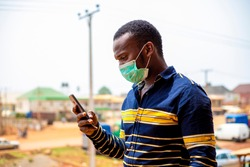 Corona virus. Africa man in mask. protecting against virus, infection. checking his mobile phone