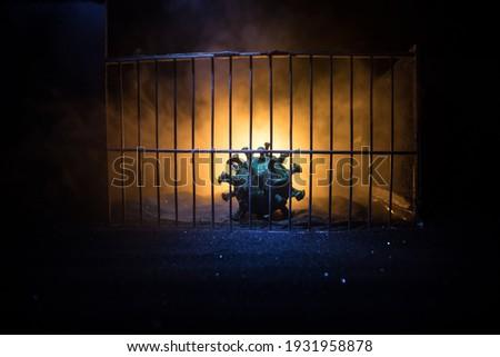 Corona virus lockdown creative concept. Corona virus novel miniature trapped inside old prison. Creative artwork decoration. Selective focus Foto stock ©