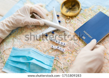 Corona virus pandemic in travel industry. travel agency working table. map, toy plane, compass, face mask and trip planning after quarantine restrictions due to epidemic covid corona virus. Tourism