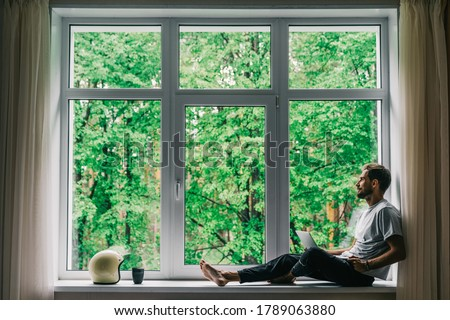 Corona virus - staying and work at home (self-isolation, self-quarantine). A self-isolated handsome man sits alone in front of a panoramic window with a laptop. Online shopping, home work, freelance.