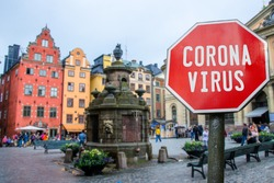 Corona virus stop sign with view of historic old town in Stockholm, Sweden. Warning about epidemic quarantine. Coronavirus disease pandemic. COVID-2019 alert sign