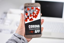 Corona Virus Tracking App concept with hand holding cell phone with application design on screen in front of blurry office background