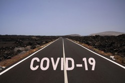 Corona virus uncertain bleak perspective symbol concept: Endless road through desert with word covid-19