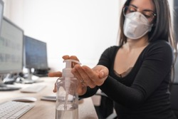 Corona Virus. Woman cleaning her hands at the office. Sick with mask for corona virus. Workplace desk with computer. Woman spraying alcohol gel or antibacterial soap sanitizer.