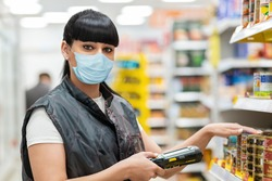 Coronavirus. A store clerk in a medical mask checks the product on the shelves using an electronic device. The concept of protection from the virus