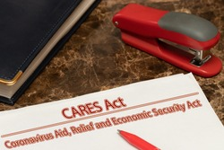 Coronavirus Aid, relief, economic security, CARES ACT text is written on a white paper against a marble table background.