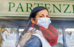 Coronavirus alarm in Italy, Europe. Woman at the airport entrance wearing respirator mask.